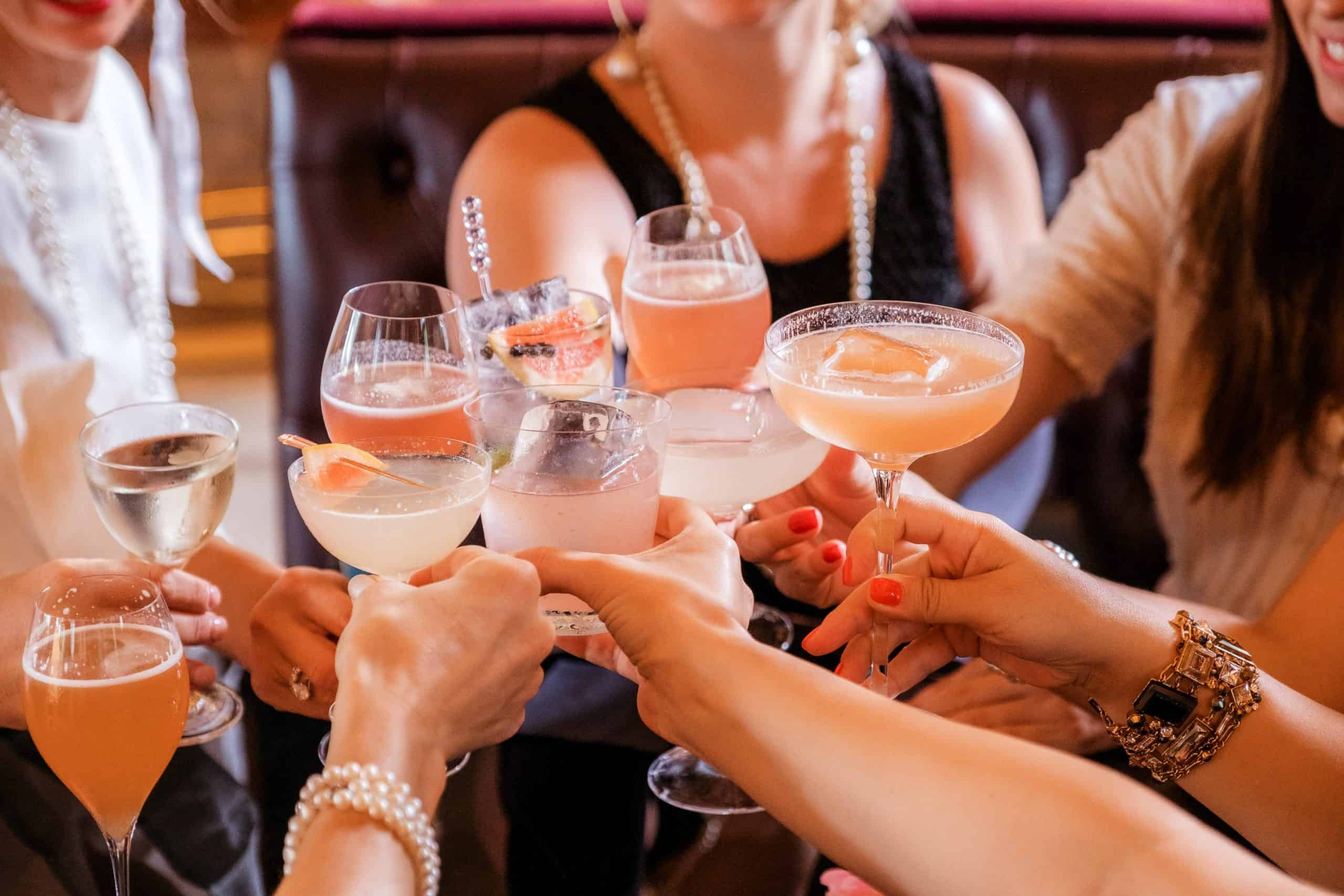 A group doing cheers with cocktails